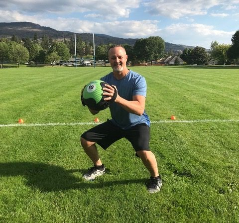James Chicalo, fitness trainer, does a squat while holding a medicine ball, doing exercise in a green field in the South Okanagan.