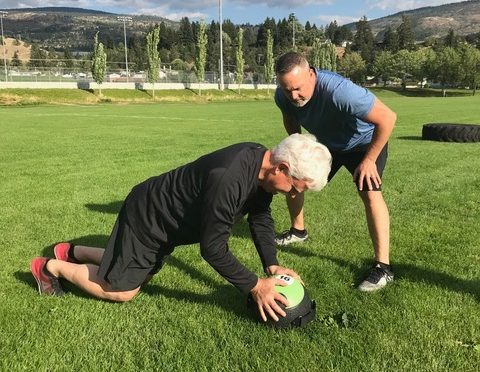 The trainer, James Chicalo, stands by, encouraging a person doing a plank during an outdoor workout in the Okanagan.