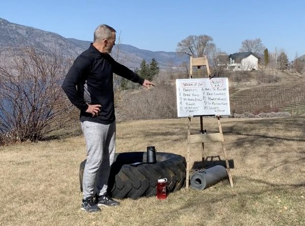 James Chicalo stands in a field overlooking Okanagan Lake, with a white board describing the HIIT workout video.